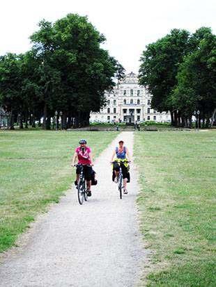 Foto: Radfahrerinnen auf einem Weg durch Wiese