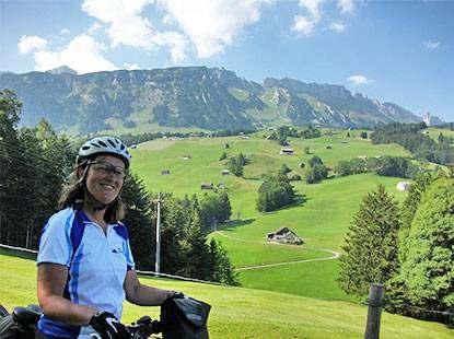 Foto2: Fit in den Radl-Sommer, Radreisen. Frau mit Fahrrad steht vor einem grünen Tal, im Hintergrund sind Berge zu sehen