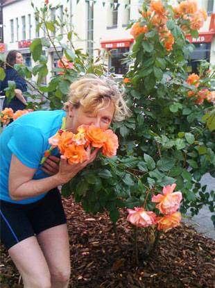 Foto 3: Radreise-Gartentraumtour, eine Frau riecht an einer Rose und lächelt